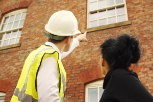 worker_pointingtobrickwallshutterstock_112356137